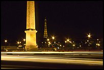 Car lights,  obelisk, and Eiffel Tower at night. Paris, France