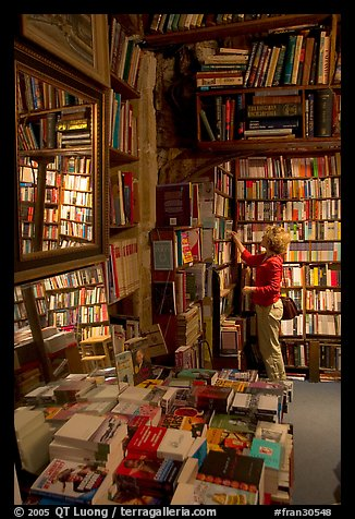 Picking-up a book in Shakespeare and Co bookstore. Quartier Latin, Paris, France (color)