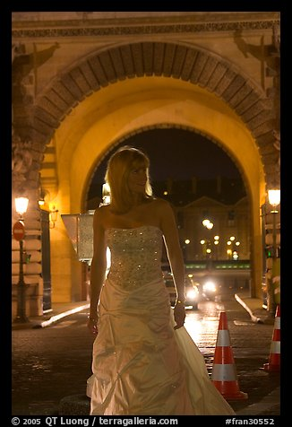 Woman in bridal gown in front of the Louvre by night. Paris, France (color)