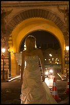 Woman in bridal gown in front of the Louvre by night. Paris, France