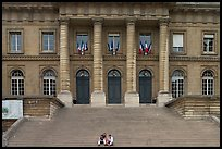 Two visitors sitting on the stairs of the Palais de Justice. Paris, France