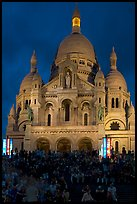 Tourists sitting on the stairs of the Sacre coeur basilic in Montmartre at night. Paris, France