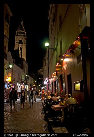 Dinners and narrow pedestrian street at night, Montmartre. Paris, France