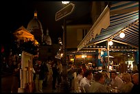 Outdoor dining at night on the Place du Tertre, Montmartre. Paris, France