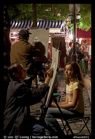 Artists drawing portraits at night on the Place du Tertre, Montmartre. Paris, France