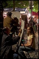 Artists drawing portraits at night on the Place du Tertre, Montmartre. Paris, France (color)