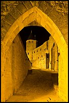 Ramparts and tower framed by gate at night. Carcassonne, France