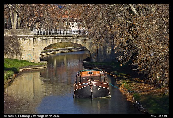 Tranquil scene with barge, bridge, and trees, Canal du Midi. Carcassonne, France