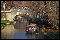Tranquil scene with barge, bridge, and trees, Canal du Midi. Carcassonne, France (color)