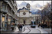Street with people walking, tramway and church. Grenoble, France