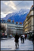 Downtown street and snowy mountains of the Belledone Range. Grenoble, France