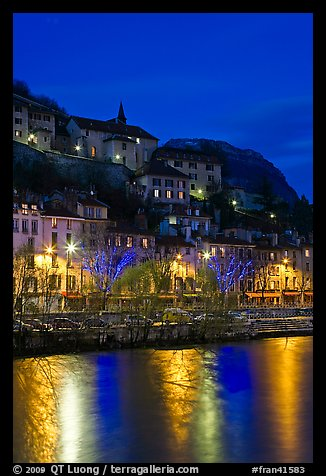 Hillside houses and Christmas lights reflected in Isere River. Grenoble, France (color)