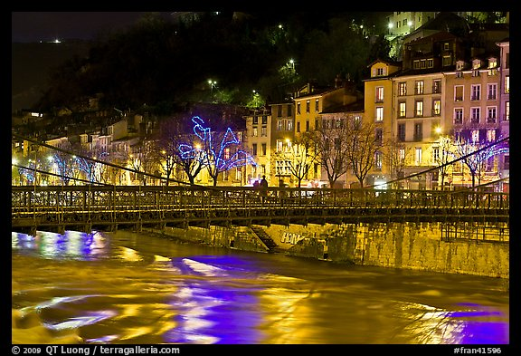 Suspension bridge at night with Christmas lights reflected in river. Grenoble, France (color)