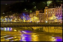 Suspension bridge at night with Christmas lights reflected in river. Grenoble, France