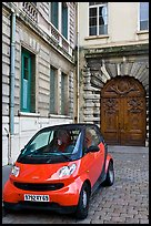 Tiny car on coblestone pavement in front of historic house. Lyon, France ( color)