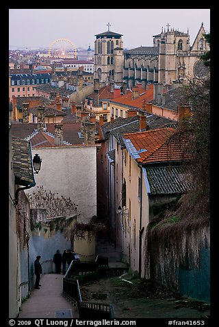 Stairs, rooftops, St-Jean Cathedral, and Ferris Wheel at dusk. Lyon, France (color)