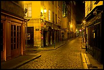 Narrow cobblestone street in historic district at night. Lyon, France