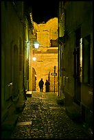 Narrow cobblestone passageway at night next to arena. Arles, Provence, France