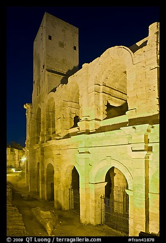 Arenes Roman amphitheater with defensive tower at night. Arles, Provence, France