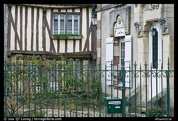 Fence, stone house, and half-timbered house, Provins. France (color)