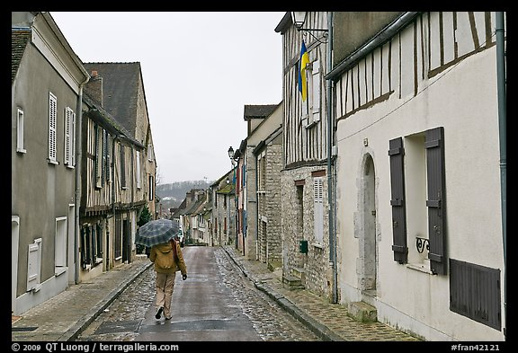 Pedestrian with umbrella in narrow street, Provins. France (color)