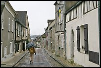 Pedestrian with umbrella in narrow street, Provins. France