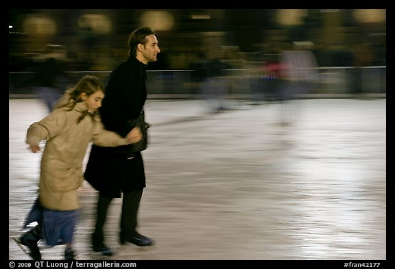 Man skating with daughter by night. Paris, France (color)
