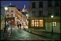 Cobblestone street, lamps, and Sacre-Coeur basilica by night, Montmartre. Paris, France