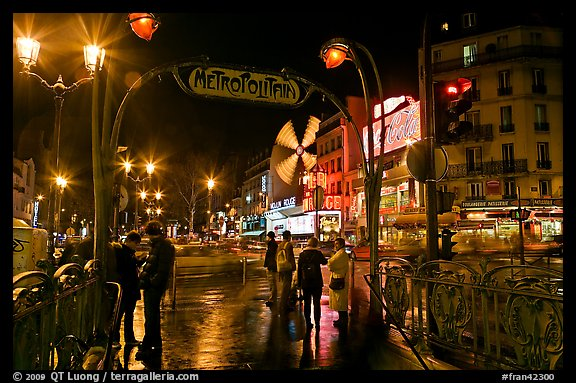 Metro entrance, boulevard, and Moulin Rouge on rainy night. Paris, France