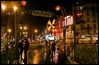 Metro entrance, boulevard, and Moulin Rouge on rainy night. Paris, France (color)