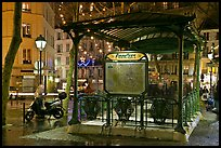 Subway entrance with art deco canopy by night. Paris, France