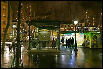 Square with subway entrance and carousel by night. Paris, France (color)