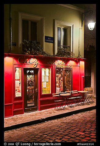 Restaurant with red facade and cobblestone street by night, Montmartre. Paris, France (color)