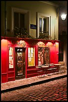 Restaurant with red facade and cobblestone street by night, Montmartre. Paris, France