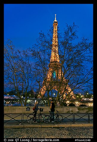 Bicyclists and Eiffel tower at night. Paris, France (color)