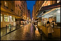 Woman buying food on street at night. Quartier Latin, Paris, France