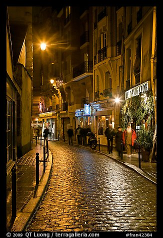 Cobblestone street with restaurants by night. Quartier Latin, Paris, France (color)