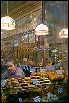 Woman selling pastries and bread in bakery. Paris, France