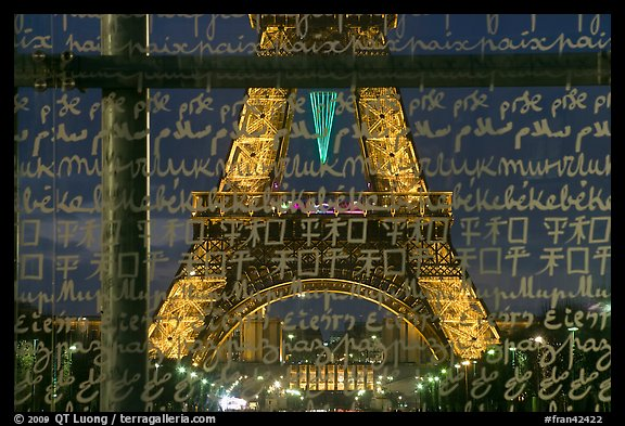 Lit Eiffel Tower seen through the words Peace written in many languages. Paris, France