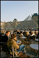 Couple sitting on terrace in Louvre main courtyard. Paris, France