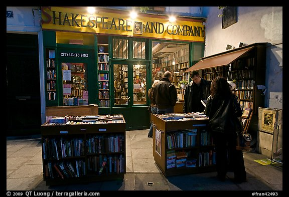 People reading in front of bookstore at night. Quartier Latin, Paris, France