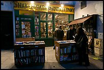 People reading in front of bookstore at night. Quartier Latin, Paris, France (color)