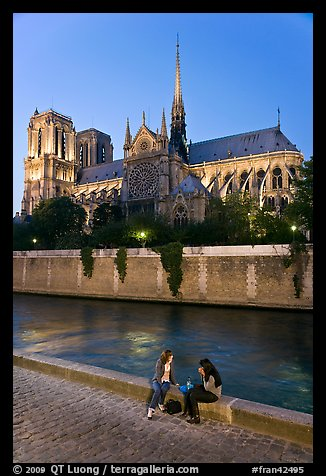 Two women having picnic across Notre Dame cathedral. Paris, France (color)