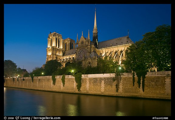 Side view of Notre Dame across Seine River at dusk. Paris, France (color)