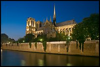 Side view of Notre Dame across Seine River at dusk. Paris, France