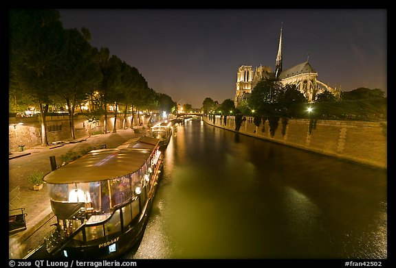 Quay, lighted boats, Seine River and Notre Dame at night. Paris, France (color)
