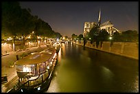Quay, lighted boats, Seine River and Notre Dame at night. Paris, France ( color)