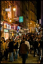 Busy pedestrian street at night. Quartier Latin, Paris, France