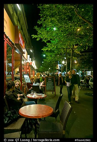 Couple walking by outdoor tables of cafe at night. Paris, France (color)