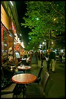 Couple walking by outdoor tables of cafe at night. Paris, France ( color)